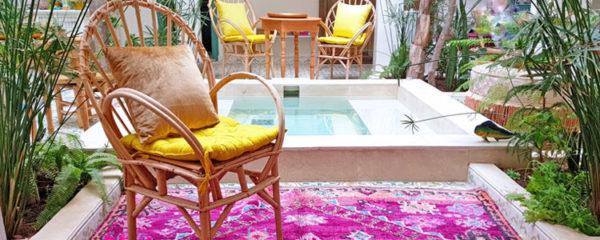 Photo d'un patio berbère en dessous d'un puits de lumière avec un tapis rose, des fauteuils en osier avec des coussins jaune et un point d'eau